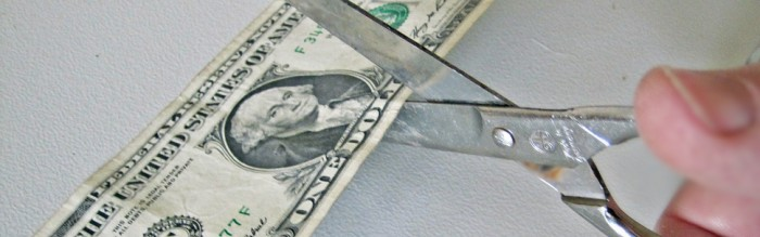 scissors cutting through a dollar bill