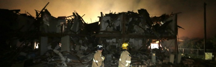 firemen searching through wreckage after plant explosion